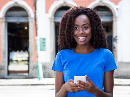 Mujer de África enviando mensaje al aire libre en ciudad africana