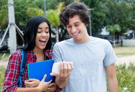 Two young adults watching video clip on mobile phone