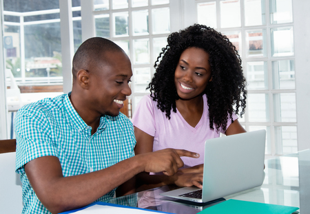 Beautiful african american couple at computer Stock Photo