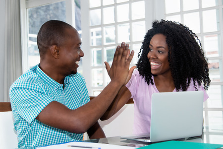 African american couple at laptop give high five