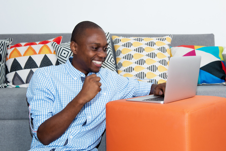 Successful cheering african american man with computer