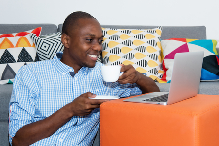 African american man watching movie clip online with laptop