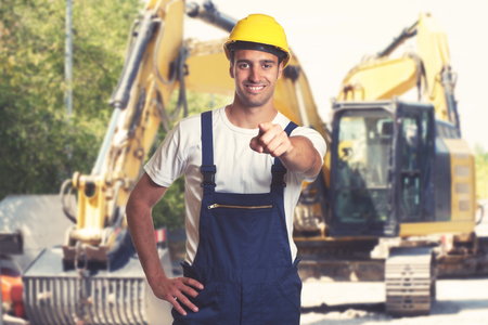 Yellow earthmover with pointing latin american construction worker Stock Photo