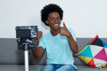 Laughing african american vlogger recording video blog Stockfoto