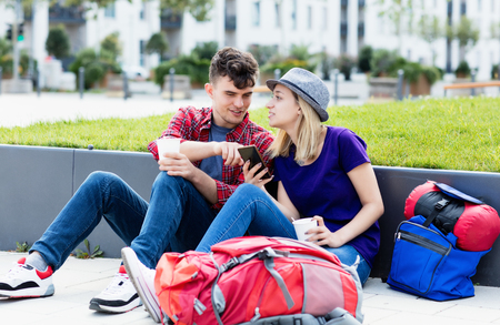 Backpacker couple looking on phone to find a hostel