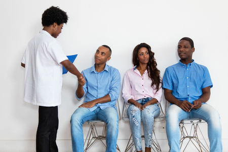 African american nurse with patients at waiting room