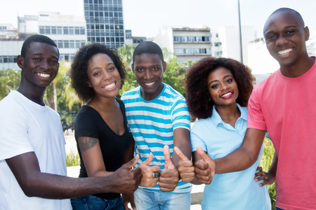 Group of successful african american men and women showing thumbs up outdoors in the summer
