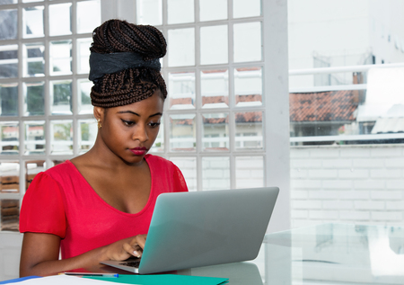 African american woman sending message with computer