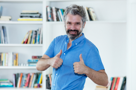 Happy middle aged man with grey hair showing both thumbs up 写真素材 - 117135913