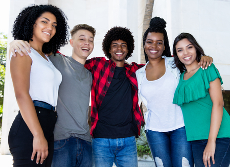 Large group of brazilian young adults arm in arm in the city