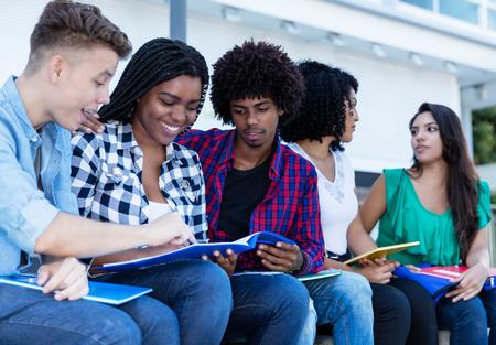 Grupo de estudiantes internacionales que aprenden al aire libre en el campus de la universidad.