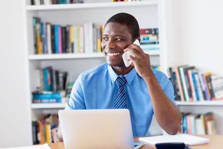 African american businessman with necktie at mobile phone at office Stock Photo