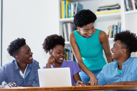 Group of african american students with female teacher at university