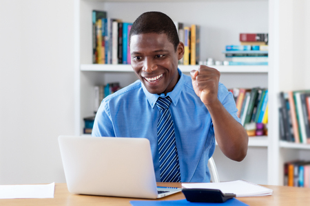 Cheering african american businessman with necktie at computer at office