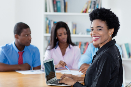 Smart african american businesswoman with team and computer at office of new business company