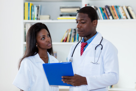 African american male doctor talking with nurse about patient