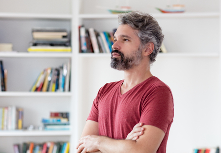 Thinking german middle aged man with grey hair indoors at home