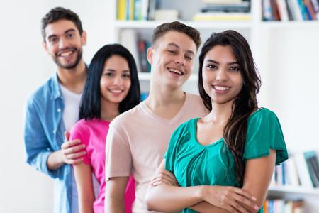 Lateinamerikanisches Mädchen mit einer Gruppe von Freunden in einer Reihe drinnen an der Universität