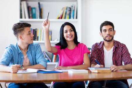 Lachende vrouwelijke student die hand opsteekt in de klas van school Stockfoto