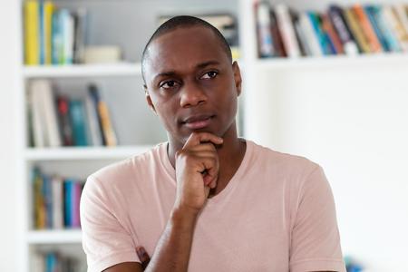 Denkende Afro-Amerikaanse man met kaal hoofd binnenshuis thuis Stockfoto