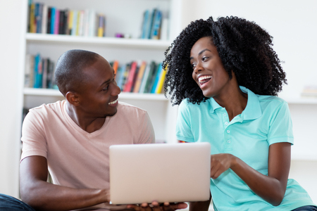 Laughing african american couple with computer indoors at home