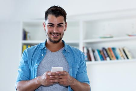 Uomo messicano hipster con la barba che invia un messaggio con il telefono al coperto a casa