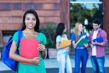 Étudiante latino-américaine riante avec un groupe d'étudiants