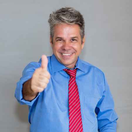 Mature businessman with grey hair showing thumb up
