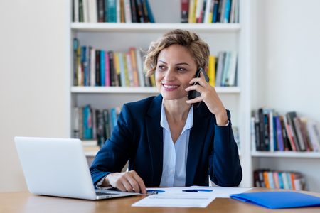 Mature businesswoman talking with client at phone