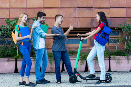 Young woman with electric scooter meeting friends