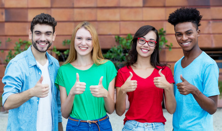 Group of four young adults of generation y showing thumbs Stockfoto