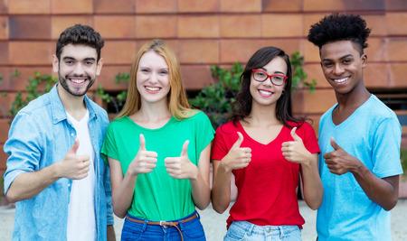 Grupo de cuatro adultos jóvenes de la generación y mostrando los pulgares