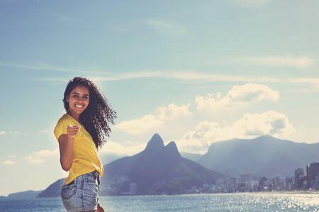 Brazilian woman with curly long hair at Ipanema beach at Rio de Janeiro