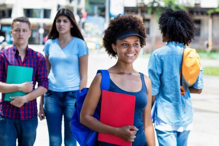 African american young adult woman with students walking in city
