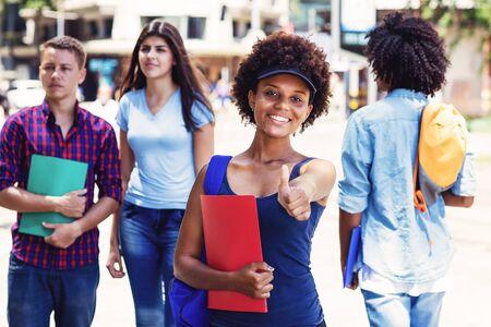Lachende afroamerikanische junge erwachsene Frau mit Studenten in der Stadt