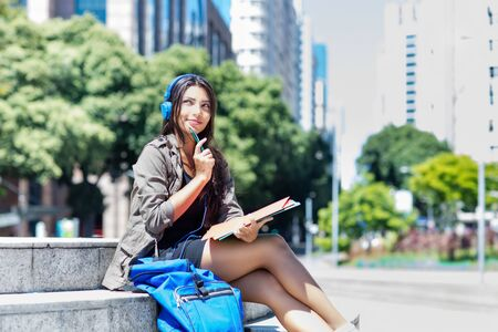 Young latin american female student with headphone in city