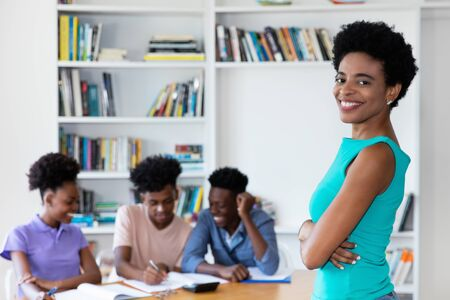 African mature teacher with students at work