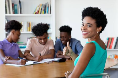 African mature tutor with students at work Stock Photo