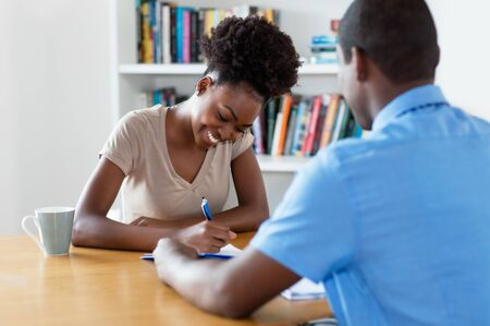 African american young adult signing contract after job interview Stock Photo