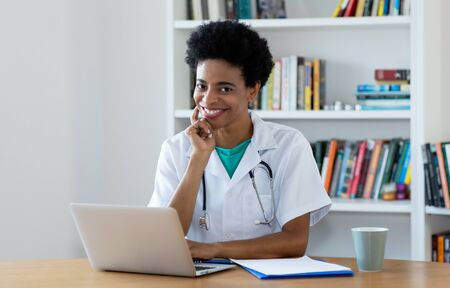 African american mature female doctor working at office