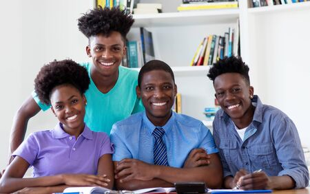 Portrait of male professor with african american students looking at camera
