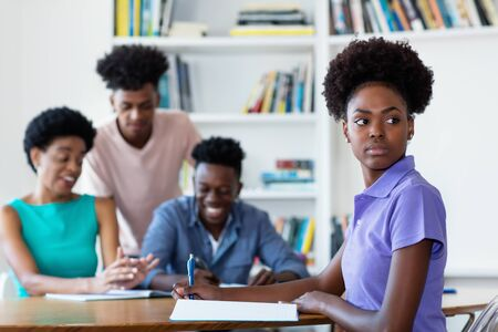 African american female student learning at desk at school