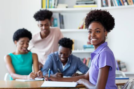 Laughing african american female student learning at desk at school