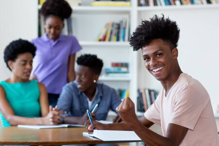 Successful african american male student learning at desk at school