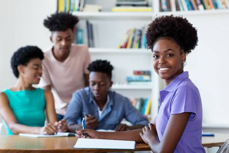 Beautiful african american female student learning at desk at school Stock Photo