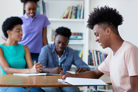 Smart african american male student learning at desk at school Stock Photo