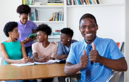 Laughing african american teacher with pupils at school