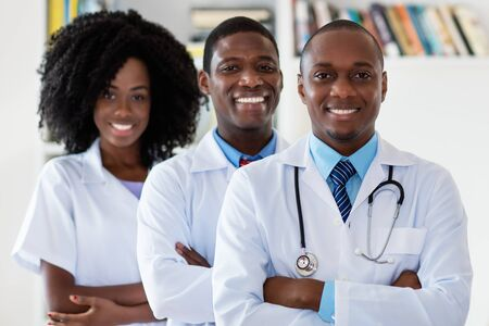 Doctor and general practitioner and nurse as african american medical team Stock Photo