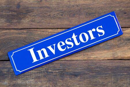 Investors street sign on wooden background
