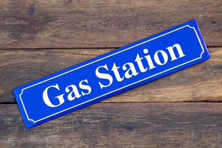 Gas station street sign on wooden background